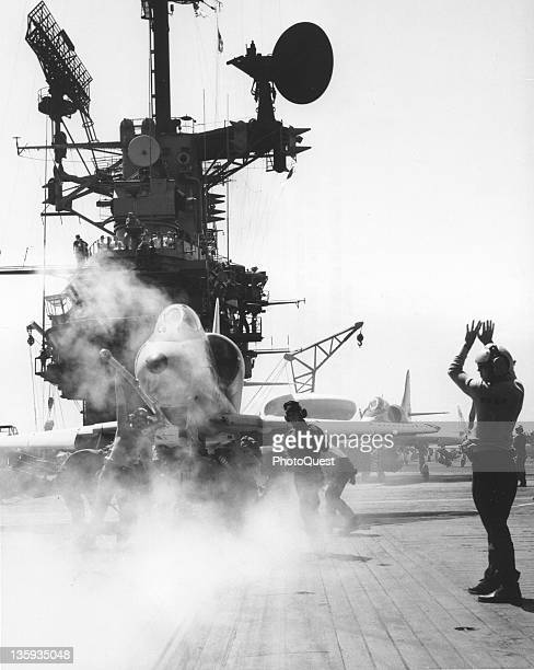 Catapult crewmen aboard the USS Hancock attach catapult bridle to an A4 Skyhawk American jetfighter while steam pressure is built up for launch...