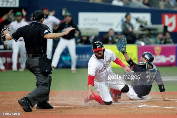Catcher Ali Solis of Mexico slides safely into home to make it 23 in the bottom of 7th inning during the game one between Japan and Mexico at Kyocera...