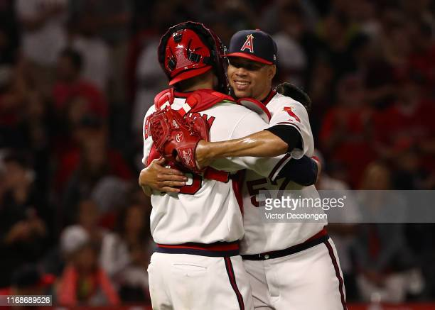 Catcher Anthony Bemboom and closing pitcher Hansel Robles of the Los Angeles Angels hug after their 65 victory against the Chicago White Sox in their...