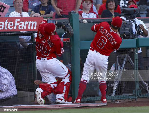 Catcher Anthony Bemboom and David Fletcher of the Los Angeles Angels can't catch the foul ball near the ondeck circle in the second inning of their...