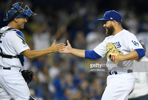 Catcher Austin Barnes of the Los Angeles Dodgers congratulates pitcher Russell Martin after Martin pitched the ninth inning of a 185 victory over the...