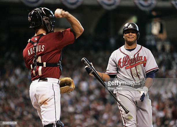 Catcher Brad Ausmus of the Houston Astros throws the ball back to the pitcher as Andruw Jones of the Atlanta Braves grimaces after swinging through a...