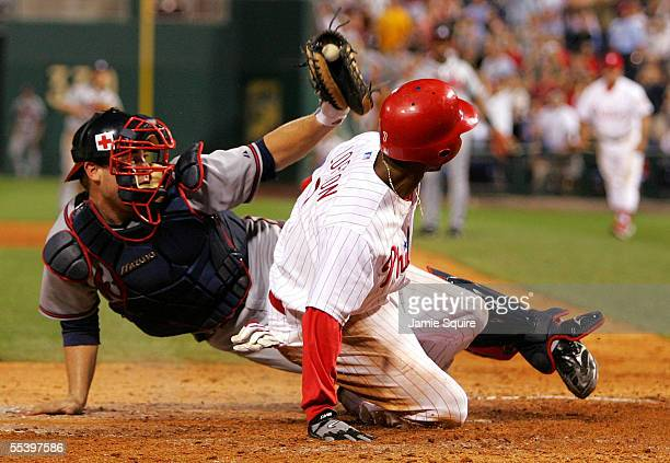 Catcher Brian McCann of the Atlanta Braves displays the ball as Kenny Lofton of the Philadelphia Phillies is called safe at home in a play at the...