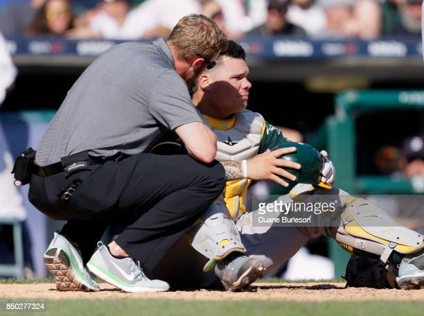 Catcher Bruce Maxwell of the Oakland Athletics is attended to by a trainer after getting hit in the face masks with a ball during the ninth inning of...
