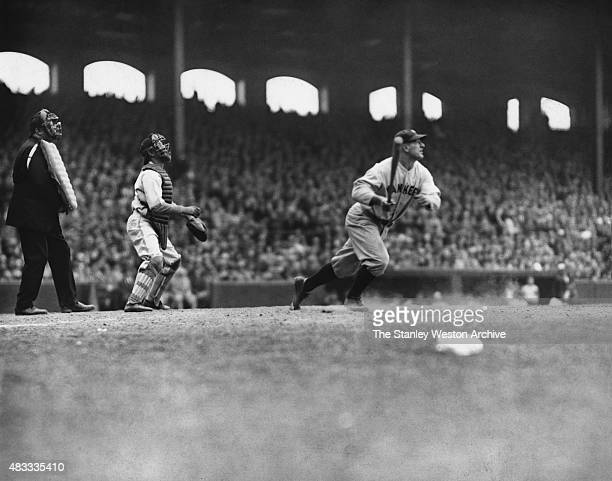 Catcher Buck Crouse of the Chicago White Sox and umpire Bill Guthrie watch as Lou Gehrig of the New York Yankees completes his swing for his third...