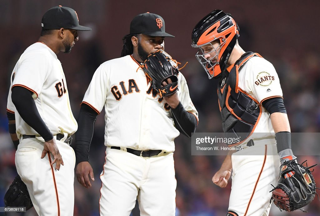 Catcher Buster Posey #28 and Eduardo Nunez #10 (L) of the San Francisco Giants comes out to talk with pitcher Johnny Cueto #47 after Cueto walks the bases loaded against the Los Angeles Dodgers in the top of the six inning at AT&T Park on April 26, 2017 in San Francisco, California.