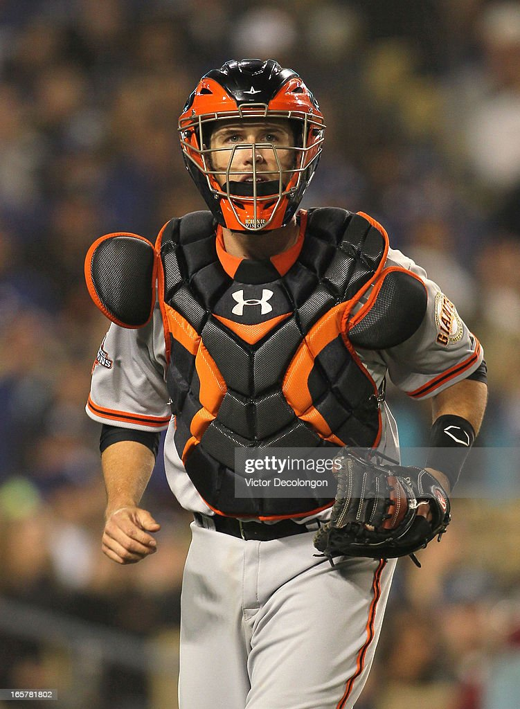 Catcher Buster Posey #28 of the San Francisco Giants jogs back to the dugout after Adrian Gonzalez #23 of the Los Angeles Dodgers (not in photo) struck out to end the sixth inning during the MLB game at Dodger Stadium on April 3, 2013 in Los Angeles, California. Posey switched from firstbaseman to catcher in the inning. The Giants defeated the Dodgers 5-3.
