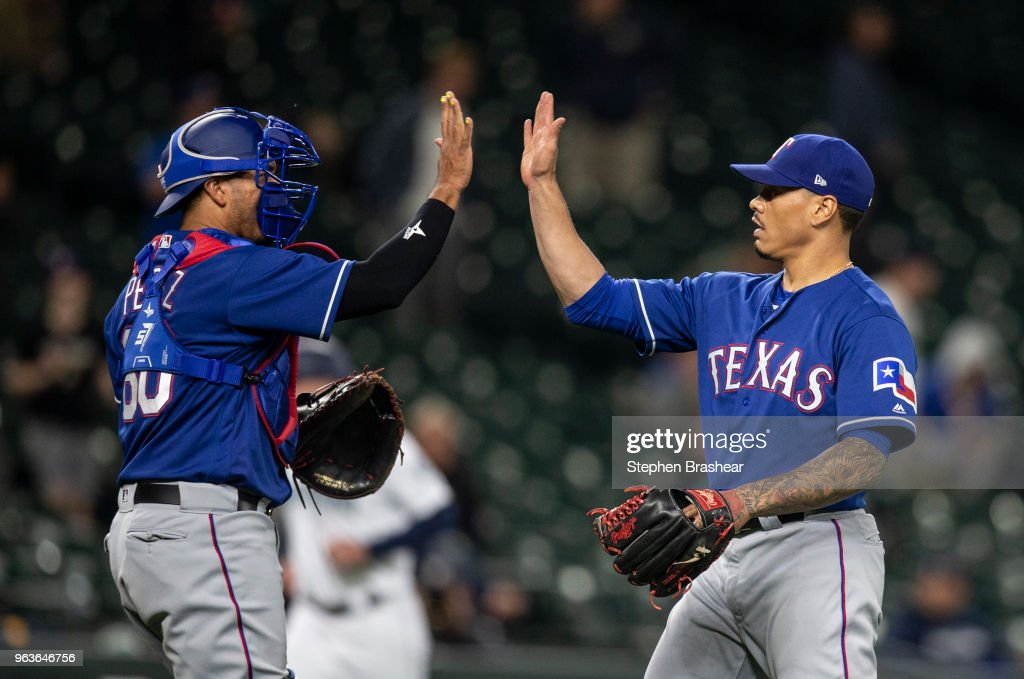 Catcher Carlos Perez #60 and relief pitcher Keone Kela #50 of the Texas Rangers celebrate after a game against the Seattle Mariners at Safeco Field on May 29, 2018 in Seattle, Washington. The Rangers won the game 9-5.
