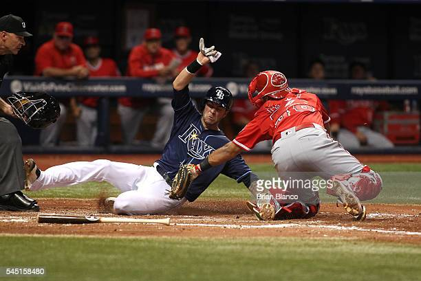 Catcher Carlos Perez of the Los Angeles Angels of Anaheim gets the out at home plate on Nick Franklin of the Tampa Bay Rays off of the fielder's...