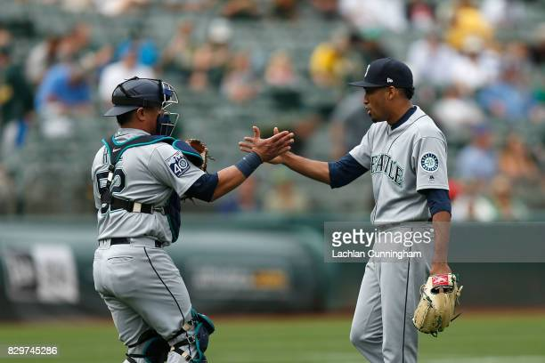 Catcher Carlos Ruiz and closing pitcher Edwin Diaz of the Seattle Mariners shake hands after a win against the Oakland Athletics at Oakland Alameda...