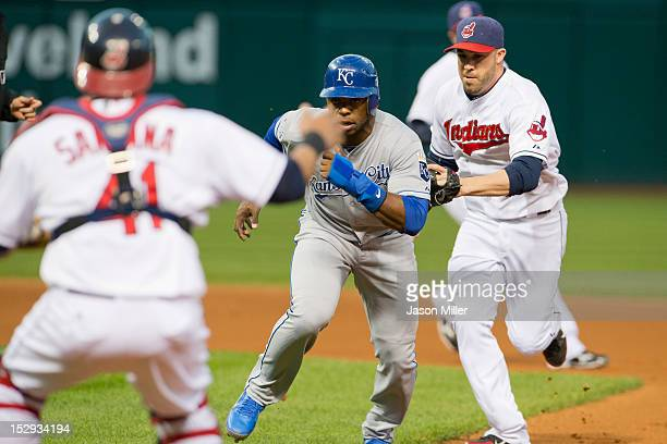 Catcher Carlos Santana and second baseman Jason Kipnis of the Cleveland Indians run down Jason Bourgeois of the Kansas City Royals in the first...