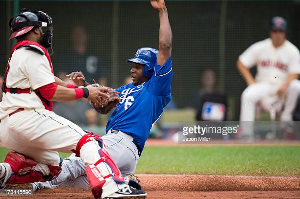 Catcher Carlos Santana of the Cleveland Indians is unable to make the tag on Lorenzo Cain of the Kansas City Royals who scored on a sacrifice fy to...