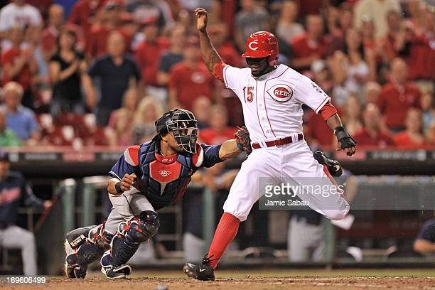 Catcher Carlos Santana of the Cleveland Indians tags out Derrick Robinson of the Cincinnati Reds at home plate in the seventh inning at Great...