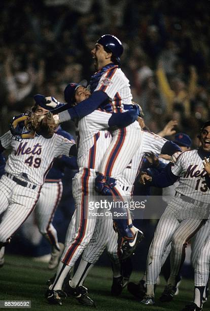 Catcher Cary Carter jumps into the arms of Pitcher Jesse Orosco of the New York Mets with jubilation after Orosco struck out Marty Berrett of the...