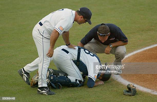 Catcher Chad Tracy of the Pepperdine Waves falls to the ground after being hit by a foul tip during the NCAA baseball regional game against the USC...