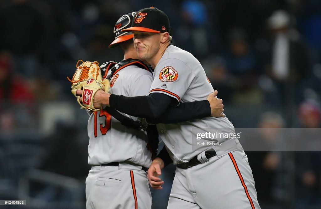 Catcher Chance Sisco #15 and Brad Brach #35 of the Baltimore Orioles embrace after defeating the New York Yankees 5-2 in a game at Yankee Stadium on April 5, 2018 in the Bronx borough of New York City.