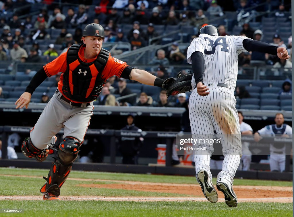 Catcher Chance Sisco #15 of the Baltimore Orioles tags out Jace Peterson #34 of the New York Yankees caught in a rundown between third base and home plate in an MLB baseball game at Yankee Stadium on April 7, 2018 in New York, NY. Yankees won 8-3.