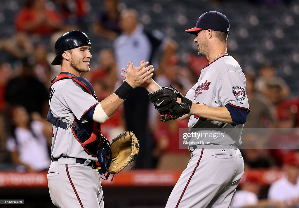 Catcher Chris Herrmann #12 and relief pitcher Josh Roenicke #20 of the Minnesota Twins celebrate after getting the final out against the Los Angeles Angels of Anaheim at Angel Stadium of Anaheim on July 23, 2013 in Anaheim, California. The Twins won 10-3 in 10 innings.