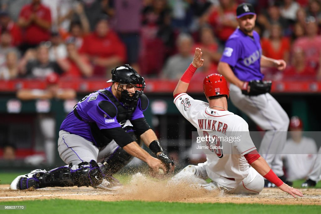 Catcher Chris Iannetta #22 of the Colorado Rockies tags out Jesse Winker #33 of the Cincinnati Reds at home plate to end the seventh inning at Great American Ball Park on June 5, 2018 in Cincinnati, Ohio. Colorado defeated Cincinnati 9-6.