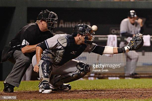 Catcher Chris Stewart of the New York Yankees takes a foul ball hit by Adam Jones of the Baltimore Orioles off the face mask in the eighth inning at...