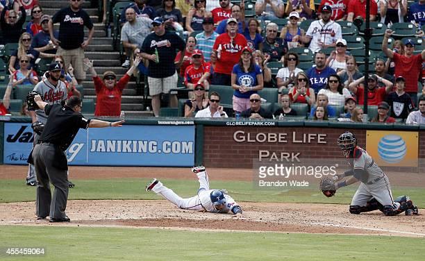 Catcher Christian Bethancourt of the Atlanta Braves looks on as home plate umpire Tony Randazzo left rules Robinson Chirinos of the Texas Rangers...