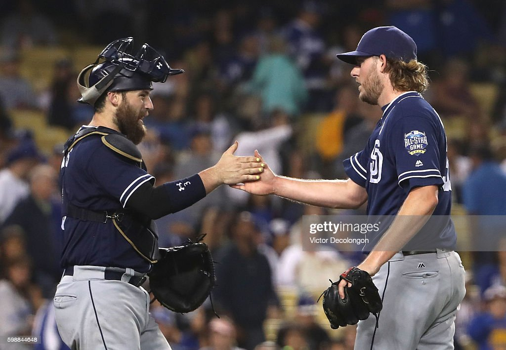 Catcher Derek Norris #3 and Brandon Maurer #37 of the San Diego Padres celebrate with a hand slap after their 4-2 win in their MLB game against the Los Angeles Dodgers at Dodger Stadium on September 2, 2016 in Los Angeles, California.