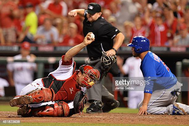 Catcher Devin Mesoraco of the Cincinnati Reds holds up the ball after tagging out Welington Castillo of the Chicago Cubs at home plate in the sixth...