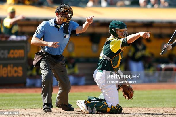 Catcher Dustin Garneau of the Oakland Athletics and home plate umpire Dan Iassogna look to the first base umpire for a decision in the ninth inning...