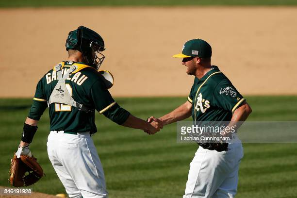 Catcher Dustin Garneau of the Oakland Athletics shakes hands with pitcher Chris Smith after a win against the Houston Astros at Oakland Alameda...