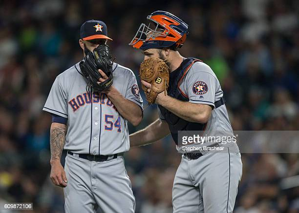 Catcher Evan Gattis, right, of the Houston Astros meets at the mound with starting pitcher Mike Fiers of the Houston Astros during a game against the...