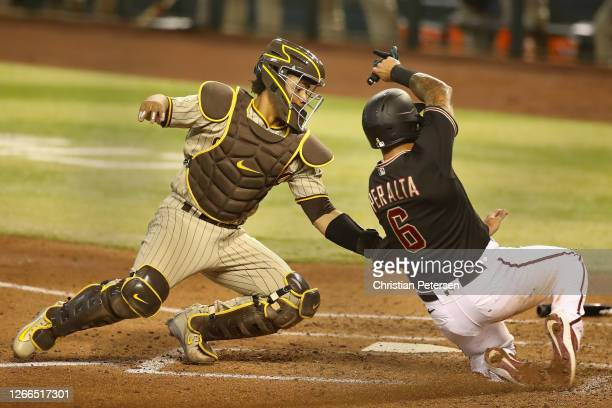 Catcher Francisco Mejia of the San Diego Padres tags out David Peralta of the Arizona Diamondbacks as he attempts to score during the fourth inning...