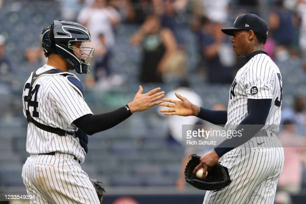 Catcher Gary Sanchez and closing pitcher Aroldis Chapman of the New York Yankees congratulate each other after defeating the Oakland Athletics 7-5...
