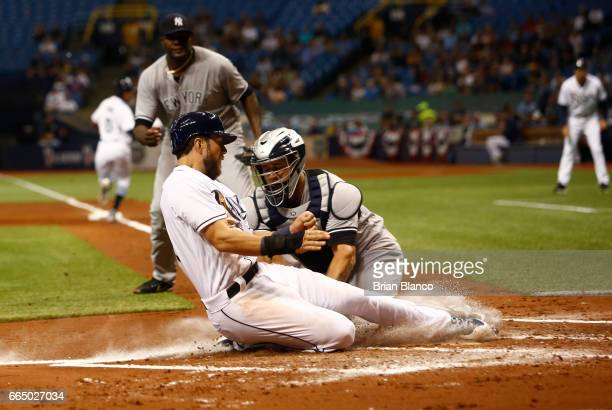 Catcher Gary Sanchez of the New York Yankees catches Steven Souza Jr #20 of the Tampa Bay Rays out at home plate as Souza attempts to score off the...