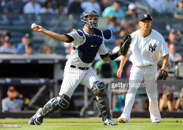 Catcher Gary Sanchez of the New York Yankees makes a throw as Masahiro Tanaka looks on during the first inning of a game against the Detroit Tigers...