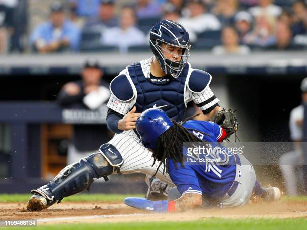Catcher Gary Sanchez of the New York Yankees reaches over as Freddy Galvis of the Toronto Blue Jays slides home under the tag in an MLB baseball game...