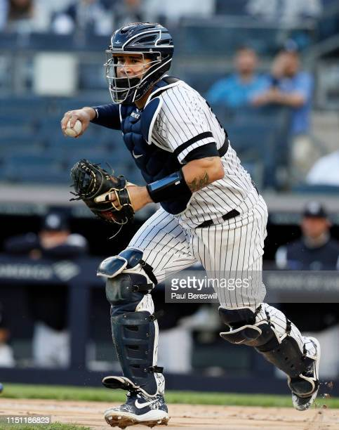 Catcher Gary Sanchez of the New York Yankees runs the ball towards third base during a rundown as Domingo Santana was caught between 3rd base and...