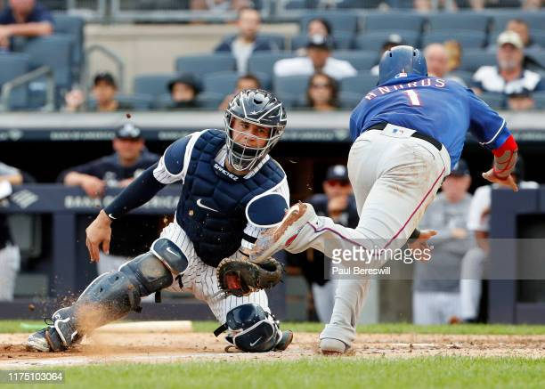 Catcher Gary Sanchez of the New York Yankees tags out Elvis Andrus of the Texas Rangers who tried to score on a single by teammate Danny Santana in...