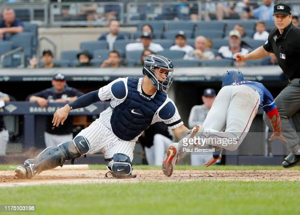 Catcher Gary Sanchez of the New York Yankees tags out Elvis Andrus of the Texas Rangers who tried to score on a single by teammate Danny Santana as...