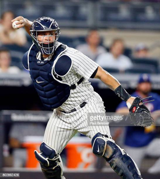 Catcher Gary Sanchez of the New York Yankees throws to first base to get a runner in an MLB baseball game against the Texas Rangers on June 23 2017...