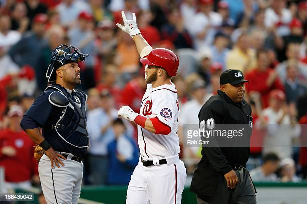 Catcher Gerald Laird of the Atlanta Braves and home plate umpire Adrian Johnson look on as Bryce Harper of the Washington Nationals celebrates...