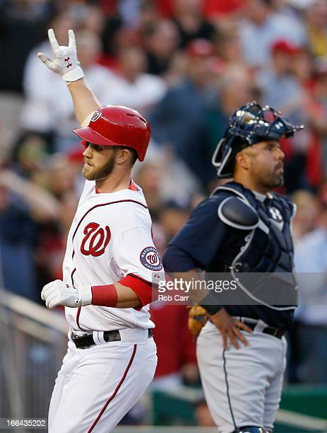 Catcher Gerald Laird of the Atlanta Braves looks on as Bryce Harper of the Washington Nationals celebrates crossing the plate after hitting a two RBI...
