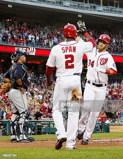 Catcher Gerald Laird of the Atlanta Braves looks on as Bryce Harper of the Washington Nationals celebrates his two RBI home run with teammate Denard...