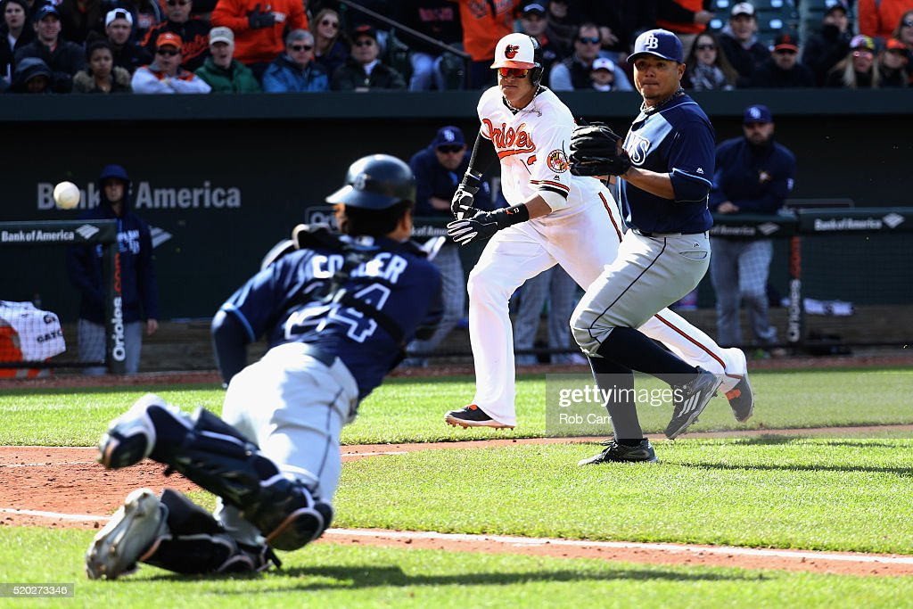 Catcher Hank Conger #24 of the Tampa Bay Rays throws to pitcher Erasmo Ramirez #30 as Manny Machado #13 of the Baltimore Orioles scroes on a wild pitch in the eighth inning of the Orioles 5-3 win at Oriole Park at Camden Yards on April 10, 2016 in Baltimore, Maryland.