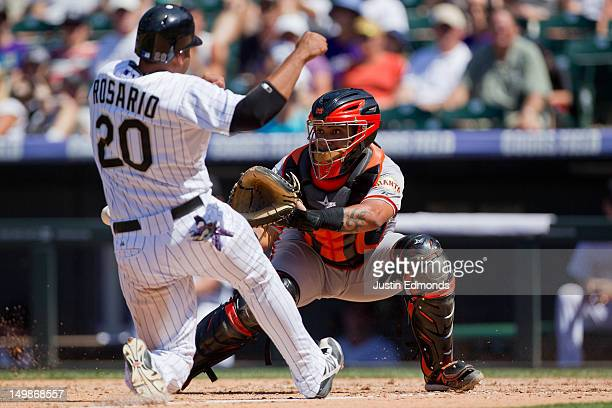 Catcher Hector Sanchez of the San Francisco Giants catches the ball at the plate and goes on to apply the tag on Wilin Rosario of the Colorado...