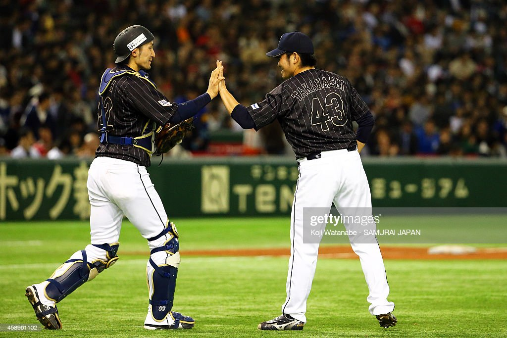 Catcher Hikaru Ito (2nd L) #22 and pitcher Tomomi Takahashi (2nd R) #43 of Samurai Japan celebrate after winning the game two of Samurai Japan and MLB All Stars at Tokyo Dome on November 14, 2014 in Tokyo, Japan.