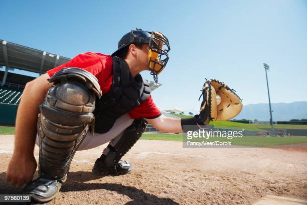 catcher holding baseball in mitt - baseball catcher stock pictures, royalty-free photos & images