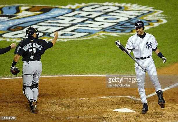 Catcher Ivan Rodriguez of the Florida Marlins pumps his fist as Derek Jeter of the New York Yankees reacts to striking out to end the fifth inning...