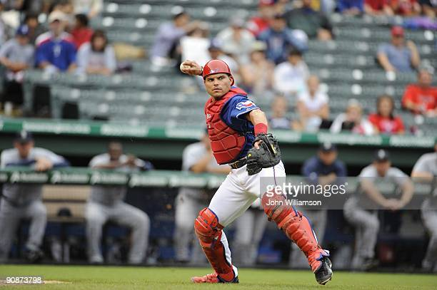 Catcher Ivan Rodriguez of the Texas Rangers fields his position as he throws to first base after fielding a ball hit out in front of home plate...