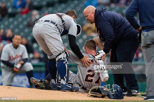 Catcher James McCann helps starting pitcher Jordan Zimmermann of the Detroit Tigers to his feat after Zimmermann was hit in the head by a line drive...