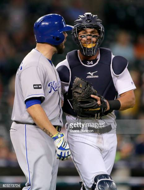 Catcher James McCann of the Detroit Tigers runs interference with Mike Moustakas of the Kansas City Royals after Moustakas was hit by a pitch from...